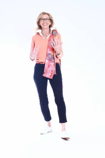 Marie står och talar engagerat med armarna i orange tröja