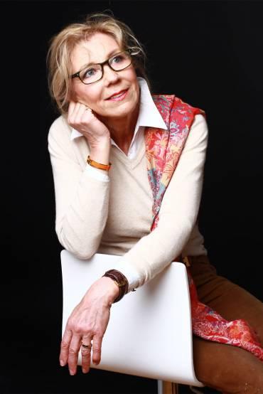 Författare Marie Mian sitter på vit stol